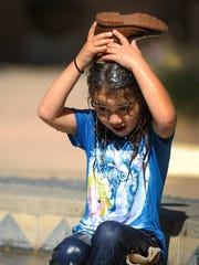 Aribella Ramos, of Ojai, uses her shoe to dump water on herself as she keeps cool and plays in the fountain at Libbey Park in Ojai on Thursday.