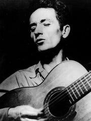 Folk singer Woody Guthrie plays his guitar.