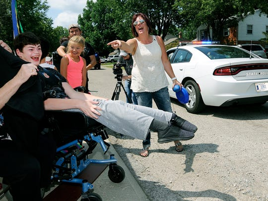 Matthew Robinette, left, reacts as a parade for his