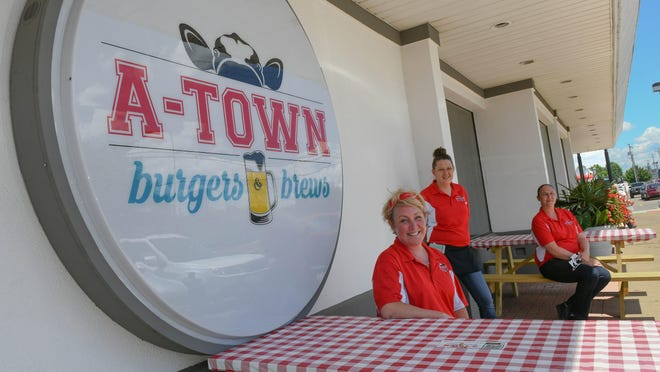 A-Town Burgers and Brews servers Shannon Weingart, Amanda Lecorchick and Lisa Minor can serve customers outside as Alliance granted the restaurant a temporary permit for outdoor dining in order to help offset the COVID-19 restrictions.