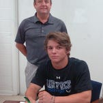 Zack Hebert is watched by father Matt Hebert during a college baseball scholarship signing ceremony Tuesday. Hebert, a former Opelousas Catholic standout third baseman, signed with LSU Alexandria last week. LSUA is a four-year university that competes athletically in the NAIA Red River Athletic Conference. Zack Hebert said he plans to play an infield position and possibly pitch for the Generals, which won 39 games last year.
