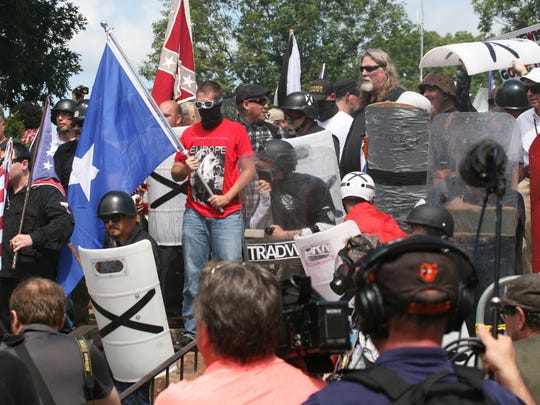 Demonstrators confront counter protesters with flags and shields.