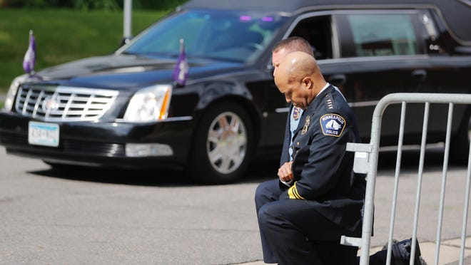 """Police officers take a knee as the body of George Floyd arrives before his memorial services Thursday in Minneapolis. """"Police are not the problem,"""" writer Jason Mott argues. """"Problem police are the problem."""""""