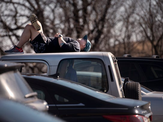 Rich Carino, of Belleville, lies on the roof of his