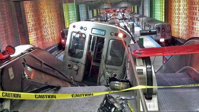 """A Chicago Transit Authority train car rests on an escalator at the O'Hare Airport station after it derailed early Monday, March 24, 2014, in Chicago. More than 30 people were injured after the train """"climbed over the last stop, jumped up on the sidewalk and then went up the stairs and escalator,"""" according to Chicago Fire Commissioner Jose Santiago. (AP Photo/NBC Chicago, Kenneth Webster) MANDATORY CREDIT ORG XMIT: NY108"""
