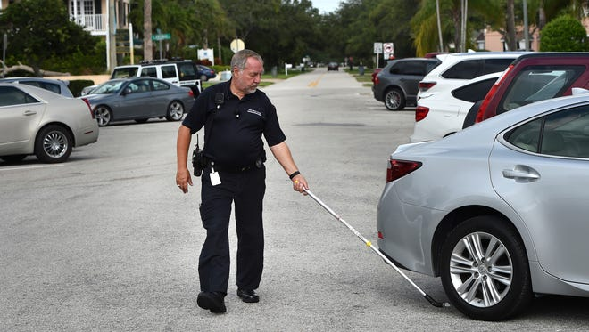 "Parking Enforcement Officer John Makolin, a non-sworn position with the city of Vero Beach, marks parked cars with a chalk stick in the two-hour parking zone along Bougainvillea Lane on March 31, 2017, in Vero Beach. ""The economy of the beach area and downtown area, traffic has got to keep moving,""  Makolin said."