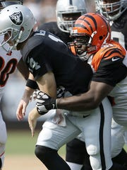 Cincinnati Bengals defensive tackle Geno Atkins (97), right, sacks and causes a fumble from Oakland Raiders quarterback Matt McGloin (14) in the third quarter during the NFL football game between the Cincinnati Bengals and Oakland Raiders, Sunday, Sept. 13, 2015, at O.co Coliseum, in Oakland, California.