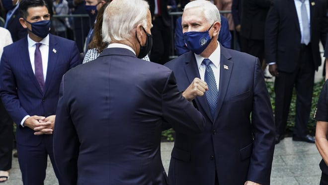 Democratic presidential candidate and former Vice President Joe Biden, left, greets Vice President Mike Pence, right, at the National September 11 Memorial and Museum, Friday, Sept. 11, 2020, in New York. Americans will commemorate 9/11 with tributes that have been altered by coronavirus precautions and woven into the presidential campaign.