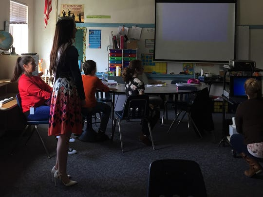 Mikayla Wood (left, standing) prepares to make a presentation