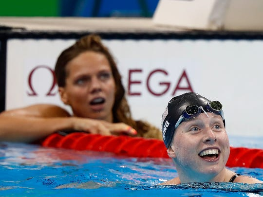 Lilly King smiles as she looks at the board with her name atop as Russia's Yulia Efimova looks on.