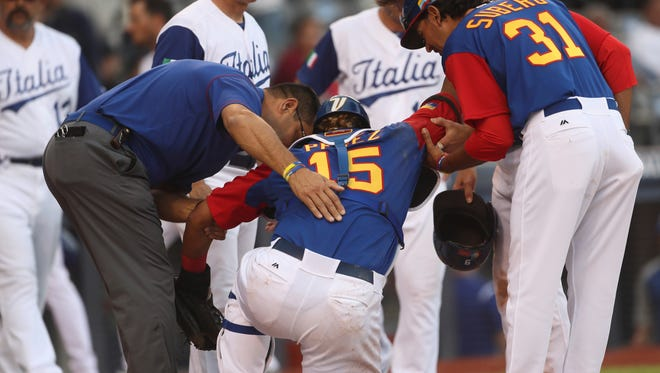 Venezuela's Salvador Perez is helped after being injured in a collision at home.