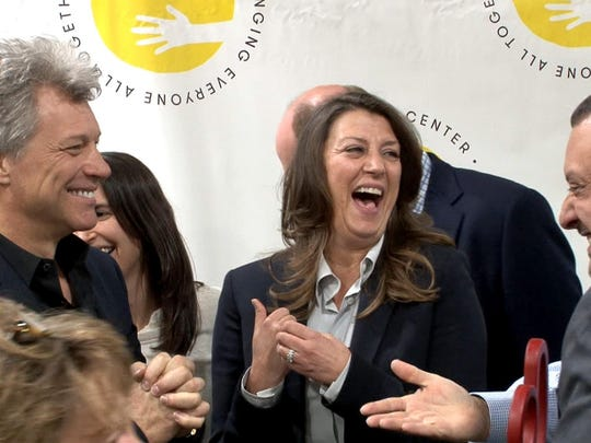 Jon Bon Jovi and his wife Dorothea laugh along with Carlos M. Rodriguez (right), executive director of the FoodBank of Monmouth and Ocean Counties, during a ribbon cutting for the BEAT Center in Toms River, NJ, Tuesday, May 10, 2016.