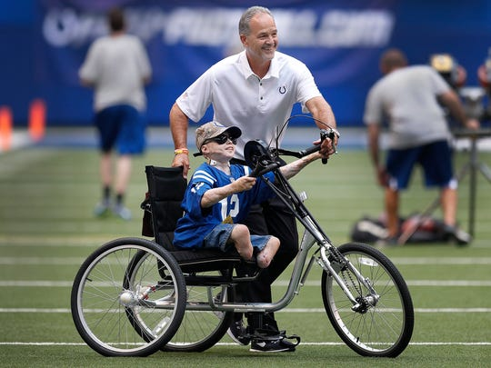 Owen Mahan, 10, from Pittsboro, gets a chance to ride his new hand-powered bike on the field at Lucas Oil Stadium with the help from Indianapolis Colts head coach Chuck Pagano before their preseason football game Thursday, August 31, 2017.  Mahan was burned over 98% of body at  the age of 2. Sons of the Flag donated the bike to Owen after meeting him during a recent FDIC convention in Indianapolis. Sons of the Flag is a non-profit group that help burn victims.