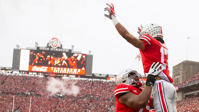 Ohio State Buckeyes wide receiver Chris Olave, top, celebrates with offensive lineman Thayer Munford after scoring a touchdown against the Michigan Wolverines at Ohio Stadium.