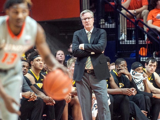 Iowa coach, Fran McCaffery and his team watch as Illinois guard Tracy Abrams controls the ball Wednesday in Champaign, Ill.