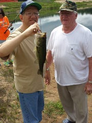 Mike Balzer of Opportunity Development Center poses with his catch and Keith Luebke of the Grand Rapids Lions Club in the summer of 2014.