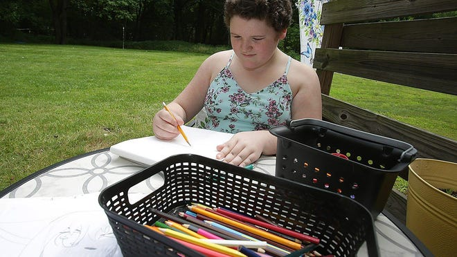 Anna Dutton, 10, uses drawing as therapy, as shown here on the back porch of her Jackson Township home. Dutton sought counseling from the CommQuest Services after the coronavirus pandemic started.