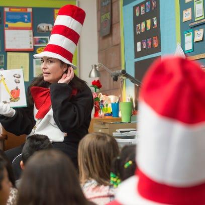 Principal Tommi Cox reads a Dr. Seuss book to a class