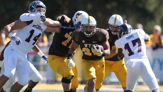 Wyoming running back Shawn Wick runs through Florida Atlantic defenders during the first half of an NCAA college football game Saturday, Sept. 20, 2014, in Laramie, Wyo.
