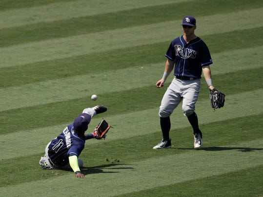 Tampa Bay Rays' Adeiny Hechavarria, left, misses a ball hit by Los Angeles Angels' Kole Calhoun as left fielder Corey Dickerson comes in to cover during the seventh inning of a baseball game, Sunday, July 16, 2017, in Anaheim, Calif. (AP Photo/Jae C. Hong)