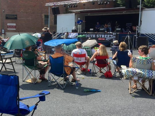 People listening to music at the eighth annual Shenandoah Valley Blues and Brews Festival on Saturday also brought umbrellas - which would serve a dual purpose at the event.