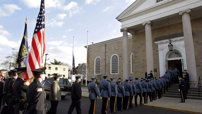 In this 2006 file photo, New York police officers file into Queen of Peace Church in North Arlington, N.J., for the funeral of retired NYPD officer James Zadroga, 34, who worked at Ground Zero in New York after the Sept. 11 terrorist attacks. A rally is being held today urging Congress to renew legislation named after Zadroga that provides health screenings and financial aid to first responders whose health was compromised by exposure at Ground Zero.  (AP Photo/Mike Derer, File)