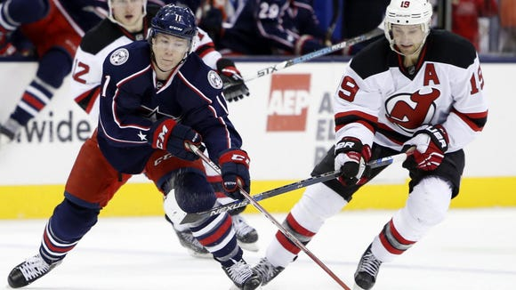 Columbus Blue Jackets' Matt Calvert, left, carries the puck up ice as Devils' Travis Zajac defends during the first period Saturday in Columbus, Ohio.