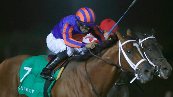 """Maximum Security, left, reaches the finish line of the $20 million Saudi Cup at King Abdul Aziz race track in Riyadh, Saudi Arabia on Feb. 29. An indictment charges Maximum Security's trainer, trainer Jason Servis, with administering a PED called SGF-1000 to """"virtually all the racehorses under his control."""""""