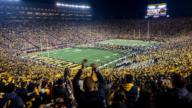 From Oct. 13, 2018, fans cheer as the Michigan team takes the field at Michigan Stadium for an NCAA college football game against Wisconsin in Ann Arbor, Mich. While professional sports leagues can ponder plans to isolate their athletes from the coronavirus and have them play in unusual, even secluded places, college sports have no such option. Pro sports leagues can get creative with solutions to save their multibillion-dollar businesses. College sports will take a slower road back.