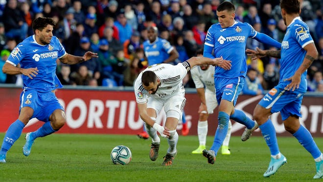 Real Madrid's Karim Benzema, center, falls during a Spanish La Liga soccer match between Getafe and Real Madrid at the Coliseum Alfonso Perez stadium in Getafe, Spain, Saturday, Jan. 4, 2020.