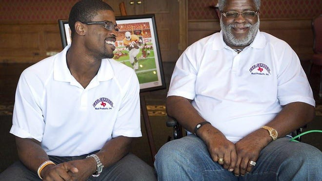 "Texas legend and NFL Hall of Famer Earl Campbell, right, and his son Tyler share a moment during an August 2012 unveiling of ""The Unstoppable Earl Campbell."""