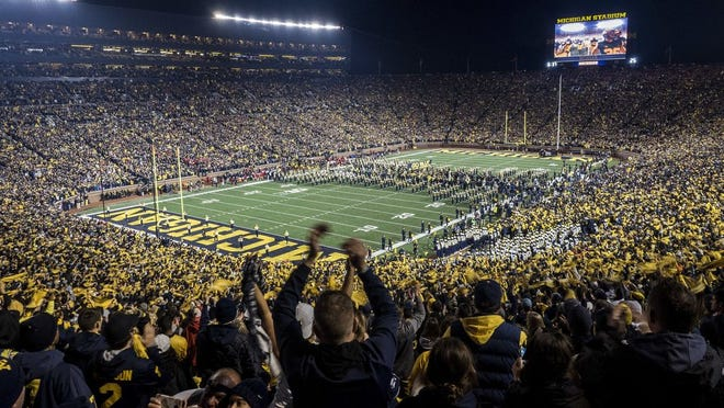 FILE - In this Oct. 13, 2018, file photo, fans cheer as the Michigan team takes the field at Michigan Stadium for an NCAA college football game against Wisconsin in Ann Arbor, Mich.