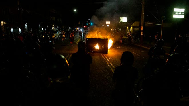 A waste receptacle is set on fire near the Portland Police Association building during a protest in Portland, Ore., on Tuesday, Aug. 4, 2020. A riot was declared early Wednesday during demonstrations in Portland after authorities said people set fires and barricaded public roadways.