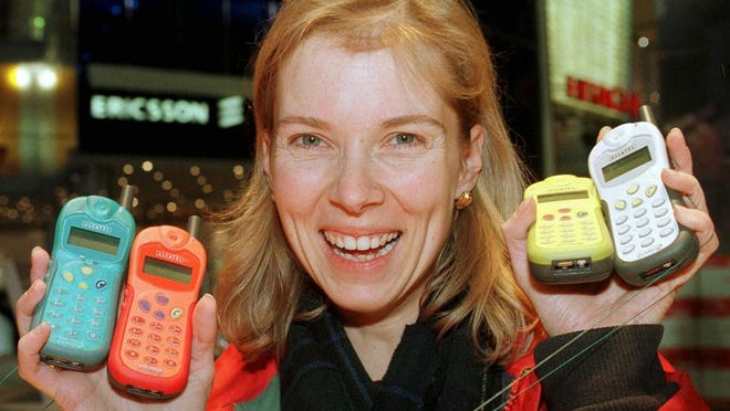 A trade fair hostess from Geneva, shows mobile phones at the Alcatel stand before the opening of the 'Telecom 99' and 'Interactive 99' exhibition in Geneva, Switzerland, Thursday October 7, 1999. The world biggest telecomunication fair will open October 10.