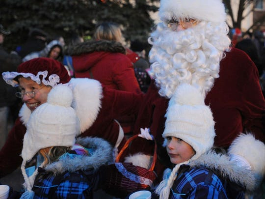Santa and Mrs. Claus pose for photos with children at the annual Greenwood Aglow.