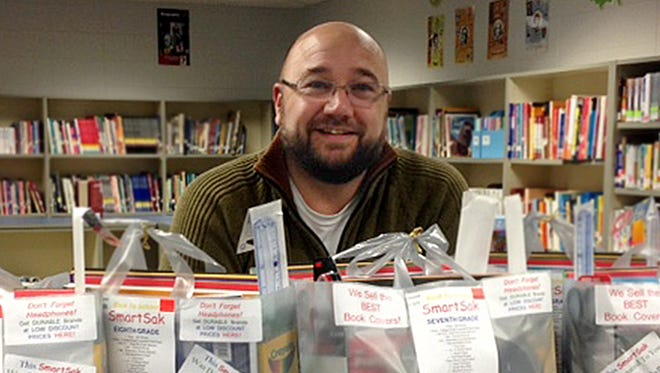 Oconto Middle School Principal Adam DeWitt poses with bags of school supplies for students in need, in 2015.