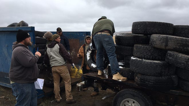 AmeriCorps volunteers unload scrap tires for a Lincoln County rancher.