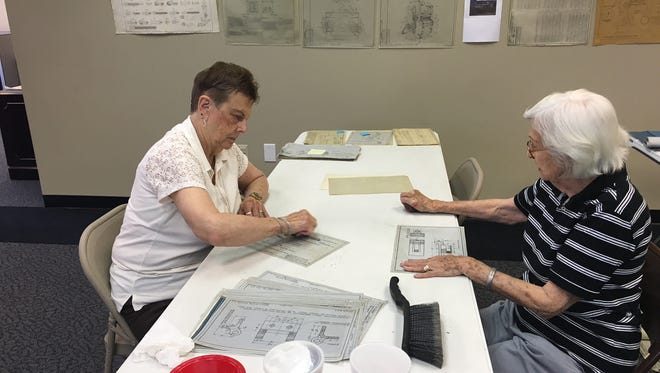 Rose Marie Silman, left, and Audrey Carlisle clean some of the historic documents.