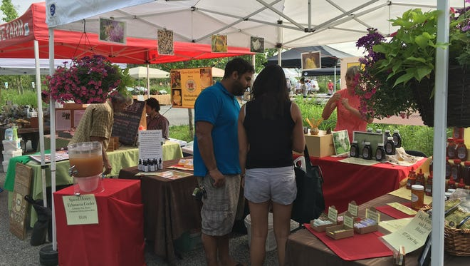 Shoppers browse the diverse range of local and artisan products in a farmer's market.