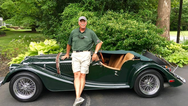 Andy Moutenot pictured with his green Morgan roadster.
