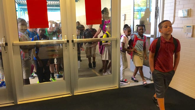 Students prepare to enter Maple Lane Elementary School for the first day of classes Thursday.