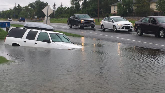 Vehicles pass a submerged car in a ditch on Highway 30 near Brightside, La., on Aug. 13. As the region cleans up after the catastrophic flooding,  lots of folks will be looking to sell their flood-damaged cars.