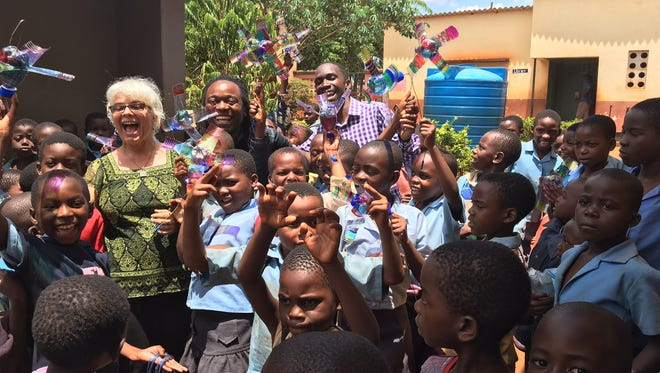 Lisa Vihos and Malawian students play with pinwheels inspired by a book on her most recent trip in December to make headway on a reading garden in Malawi.