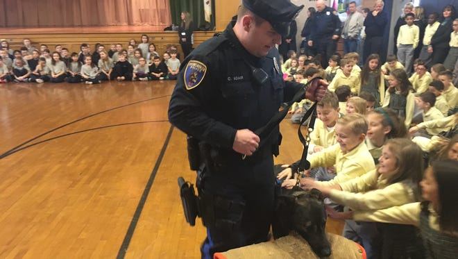 Pennsauken Police Officer Craig Adair takes K-9 Maverick around to greet students on Thursday at Our Lady of Good Counsel School. Students at the school raised more than $4,500 to help buy ballistic vests for the two K-9 officers at the department.