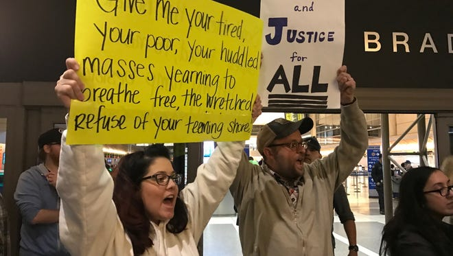 Stephanie Harper and Amato Recine, both from Ventura, protest President Donald Trump's move to ban immigration from several mainly Muslim countries. They were participating in a demonstration Saturday night at Los Angeles International Airport.