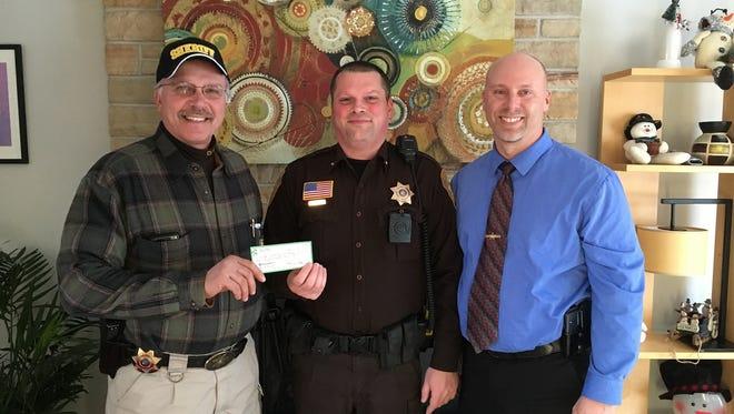 Clark County Sheriff Greg Herrick, left, and Chief Deputy James Hirsch, right, present a check for $545 to K-9 handler, Deputy Matthew Prein.