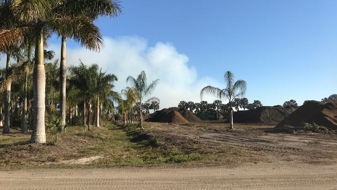 Remains of a mulch fire continue to smolder and produce smokey conditions west of the Buckingham landscaping business where the fire started Monday.