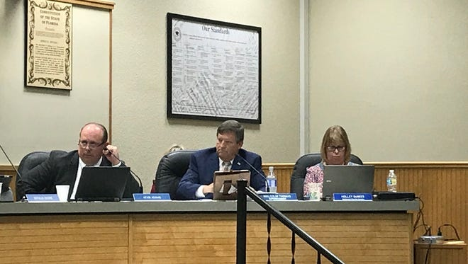 From left, Escambia County School District board member Kevin Adams, Superintendent Malcolm Thomas and Jackie Dwelle, the office administration assistant, sit at a school board meeting on Friday, April 14, 2017, in Pensacola.