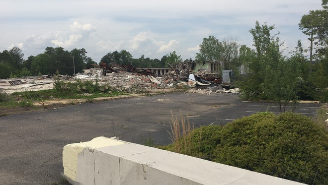 Demolition work was halted in August after asbestos was found on the site. The cleanup of the debris pile remains undecided.