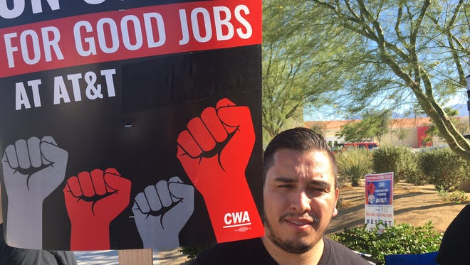 Jesus Gonzalez, an AT&T sales consultant, holds a sign with other striking workers in Indio.